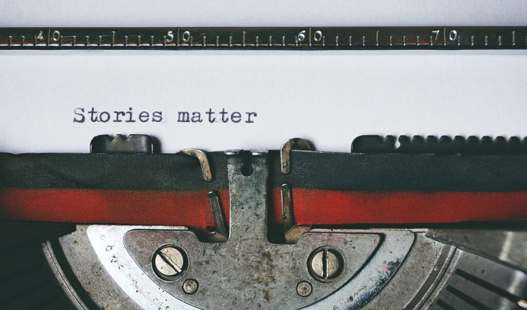 """Image is of a typewriter with a sheet of paper with text on it saying """"Stories matter"""""""