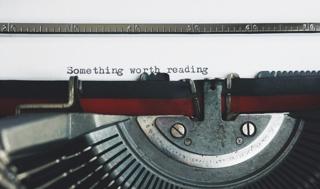 """Image is of a typewriter with a sheet of paper with text on it saying """"Something worth reading"""""""